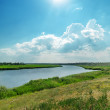 Green landscape with river and cloudy sky with sun — Stock Photo