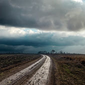 Dirty road to cloudy horizon — Stock Photo