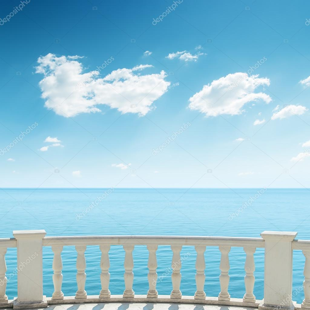 View to the sea from a balcony under cloudy sky wall mural *.
