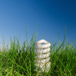 Energy saving bulb in green grass under deep blue sky — Stock Photo