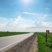 Asphalt road under sun in sky — Stock Photo