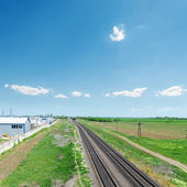 Railroad in green fields and blue sky — Stock Photo