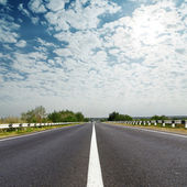 Cloudy sky over asphalt road — Stock Photo