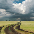 Rainy clouds over field with road — Foto Stock
