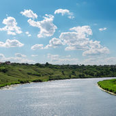 Blue sky with clouds and river with reflections — Stock Photo