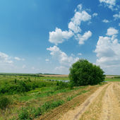 Dirty road in green landscape and blue cloudy sky — Stock Photo