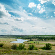 Green landscape with river and cloudy sky — Stock Photo #30487653