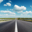 Black asphalt road to horizon under deep blue cloudy sky — Stock Photo