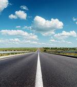 Horizon derin mavi bulutlu gökyüzü altında siyah asfalt yol — Stok fotoğraf
