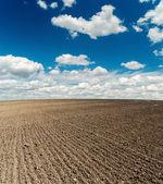 Zwarte geploegd veld na de oogst en blauwe bewolkte hemel — Stockfoto