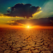 Dramatic sunset over drought earth — Stock Photo
