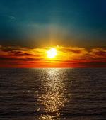 Dramatic sunset over dark water — Stockfoto