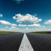 Asphalt road to horizon in deep blue cloudy sky — Stock Photo