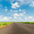 Cloudy sky and asphalt road to horizon — Stock Photo
