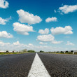 Asphalt road under blue cloudy sky — Stock Photo