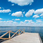 Wooden floor on river and deep blue sky — Stock Photo