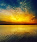 Fantastyczne zachody słońca nad wodą ciemny — Zdjęcie stockowe