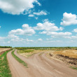 Two dirty roads under blue cloudy sky — Stock Photo #32912373