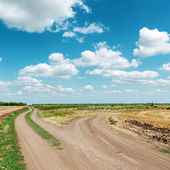 Two dirty roads under blue cloudy sky — Stock Photo