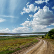 Winding country road and clouds in blue sky — Stock Photo