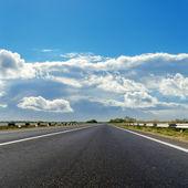 Asphalt road to cloudy horizon — Stock Photo