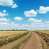 Country road in field and clouds in blue sky — Stock Photo