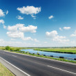 Aspalt road near river under cloudy sky — Stock Photo