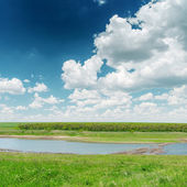 River in green grass and clouds in blue sky — Zdjęcie stockowe