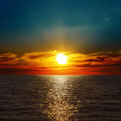 Red dramatic sunset over darken sea — Stock Photo