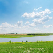 Blue sky over river and green grass — Stock Photo
