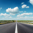 Asphalt road to horizon under cloudy sky — Stock Photo