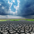 Global warming. cracked earth and dark clouds — Stock Photo #36542047