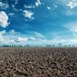 Deep blue sky with clouds and black agriculture field — Stock Photo