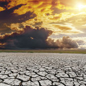 Orange dark sunset over drought earth. global warming — Stock Photo