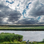 Low darken clouds over river — Stock Photo