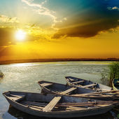 Yellow sunset over river with boats — Stock Photo