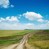 Dirty road and blue sky with clouds — Stockfoto
