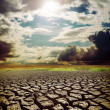 Stock Photo: Hot sun over drought earth with cracks