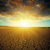 Dramatic sunset over cracked desert — Stock Photo