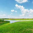 Green grass, river and clouds in blue sky — Stock Photo #38755125