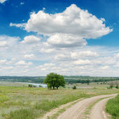 Dirty road in green meadow and clouds over it — Stock Photo