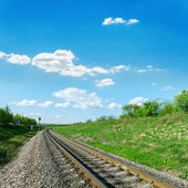 Railroad in green landscape and blue sky — Stock Photo