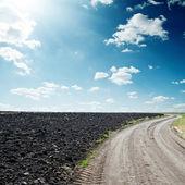 Sun in dramatic sky over road near black field — Stok fotoğraf