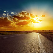 Orange sunset over asphalt road — Stock Photo
