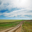 Rural road in green fields and cloudy sky — Stock Photo #41296119