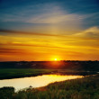 Last sunrays in sky over river — Stock Photo