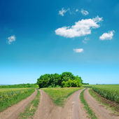 Crossing of two rural road and deep blue sky — Stock Photo