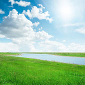 Sun in cloudy sky over river with green sides — Stock Photo