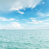 Blue water and cloudy sky over it — Stock Photo