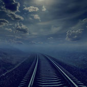 Railroad in night to horizon in fog. moonlight in cloudy sky — Stock Photo